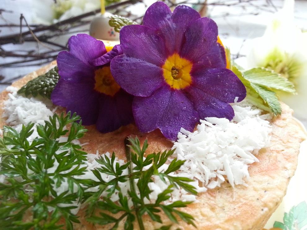 Rohkost zu Ostern mit Rüblitorte, dekoriert mit essbaren Primeln